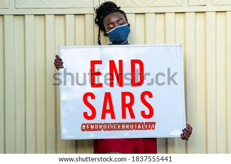 A millennial African woman wearing face mask and holding a sign with end SARS inscription - concept on human rights and police brutality Royalty-Free Stock Photo #1837555441