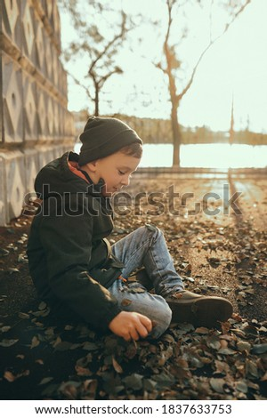 stylish school-age boy in knitted hat and Hakki color jacket sitting on road with dry leaves alone in an autumn Park, vertical frame, tinted Royalty-Free Stock Photo #1837633753