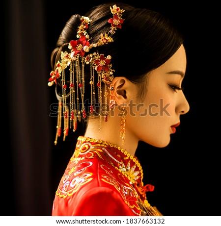 Beautiful Asian woman in wedding dress in dark background Royalty-Free Stock Photo #1837663132