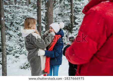 Family photo shoot in the winter snow forest for a beautiful woman and a cute girl on your smartphone.