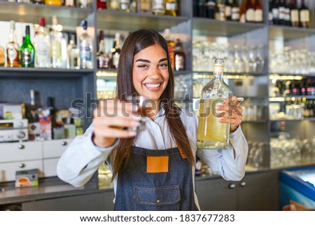 Beautiful female bartender is holding a shot glass with alcohol drink and a bottle in other hand, looking at camera and smiling while standing near the bar counter in cafe #1837677283