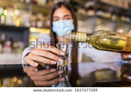 Beautiful female bartender with protective face mask pouring alcohol into shot glass during coronavirus pandemic, shelves full of bottles with alcohol on the background #1837677289