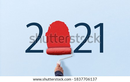 hand holds paint roller and painting 2021 year on wall. happy new year 2021.  Royalty-Free Stock Photo #1837706137