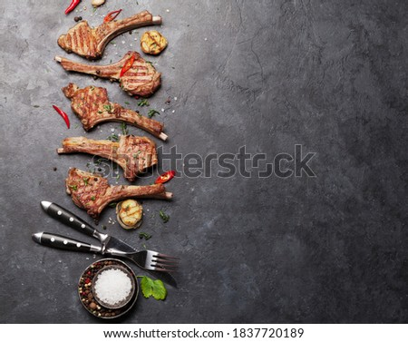 Grilled lamb ribs. Hot rack of lamb with spices and condiments. Top view on stone table with copy space Royalty-Free Stock Photo #1837720189