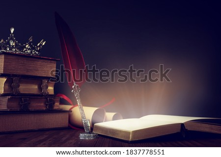low key image of beautiful queen/king crown, old books and feather quill ink pen over wooden table. fantasy medieval period Royalty-Free Stock Photo #1837778551