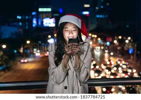Pretty Asian girl wearing Christmas hat using mobile phone outdoors in the city during Christmastime at night