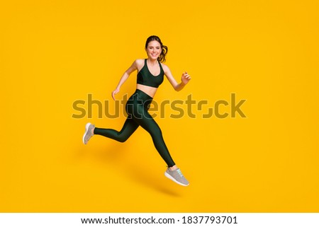 Full length profile photo of lady jump high up training marathon finish line wear sports suit shoes isolated yellow color background