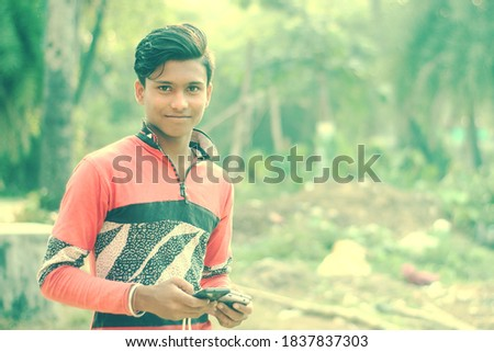 An Indian man using a smartphone and posing to the camera. Shallow dof image.