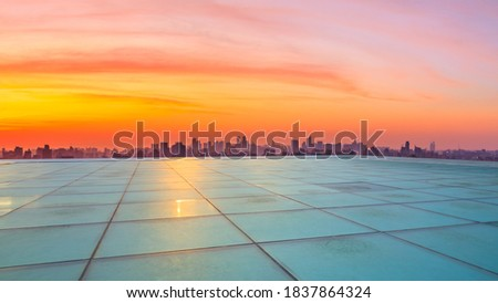 Wide square floor and city skyline with buildings in Hangzhou at sunrise.