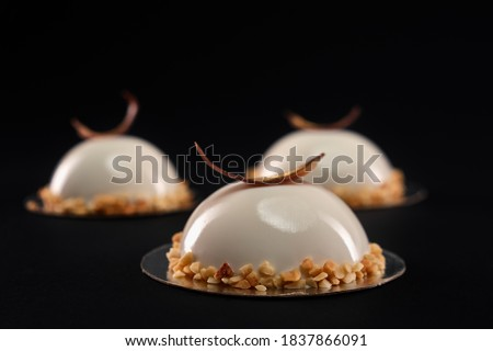 Selective focus of white half sphere cake decorated with nuts and chocolate feather. Desserts with smooth surfaces and mirror glaze isolated on black background. Tasty sweet dish in cafeteria. Royalty-Free Stock Photo #1837866091