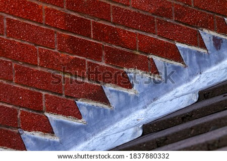 Stepped lead flashing roof gulley creating a water tight seal between roof tiles and brick wall on a domestic house Royalty-Free Stock Photo #1837880332
