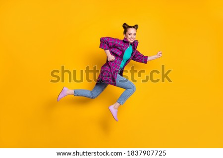 Full length profile photo of pretty teen lady jump high up run race marathon excited winner competition leader wear casual plaid shirt sneakers jeans isolated yellow vivid color background