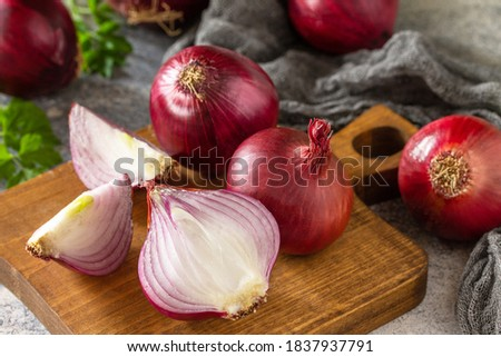 Purple Onions. Fresh whole purple onions and one sliced onion on a stone countertop. Royalty-Free Stock Photo #1837937791