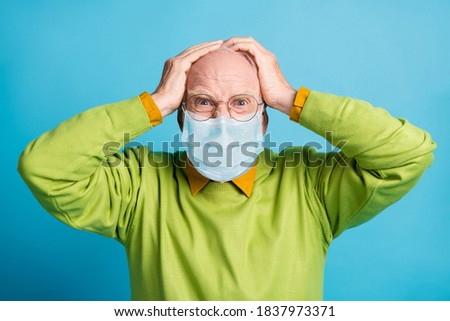 Photo of aggressive old man hands head mad look wear blue face mask isolated blue color background Royalty-Free Stock Photo #1837973371