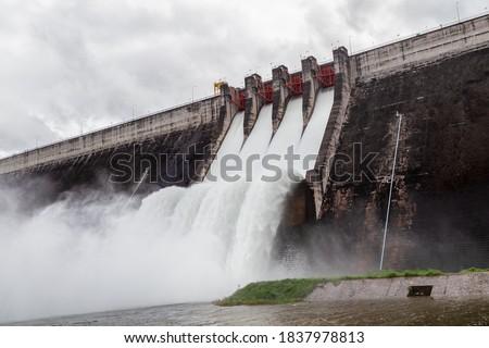 Water flowing over floodgates of a dam at Khun Dan Prakan Chon, Nakhon Nayok Province, Thailand  Royalty-Free Stock Photo #1837978813