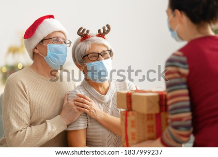 People with gifts wearing facemasks during coronavirus and flu outbreak on Christmas. Virus and illness protection, home quarantine. COVID-2019 Royalty-Free Stock Photo #1837999237