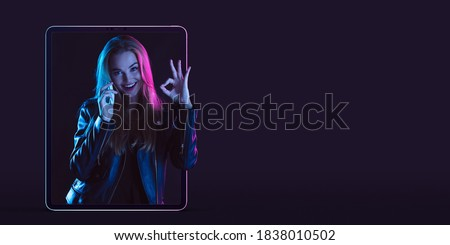 Beautiful woman inviting for shopping right from device screen, black friday, sales concept. Flyer. Cyber monday and online purchases, negative space for ad. Finance and money. Dark neon background. Royalty-Free Stock Photo #1838010502