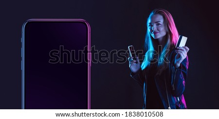 Beautiful woman inviting for shopping near by device screen, black friday, sales concept. Flyer. Cyber monday and online purchases, negative space for ad. Finance and money. Dark neon background. Royalty-Free Stock Photo #1838010508