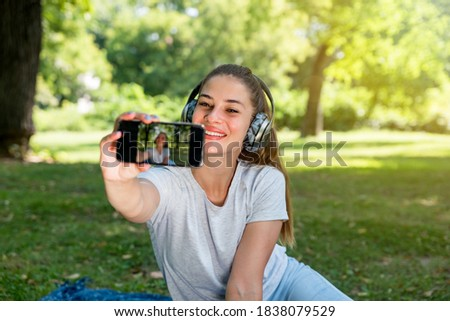 Young beautiful happy smiling woman taking selfie with her smartphone in the park while she listening the music over wireless headphones