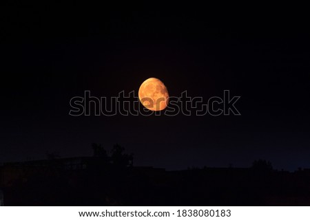 Bright orange moon in waning gibbous phase rising up on dark clear night sky above dark city silhouette. Mystic nighttime black sky with large moon, dark tranquility Royalty-Free Stock Photo #1838080183
