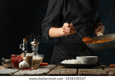 Close-up view of chef pours by ladle chicken curry from pan wok to white bowl. Backstage of serving traditional Indian curry with boiled rice on black background. Concept of cooking tasty hot meal. Royalty-Free Stock Photo #1838108107