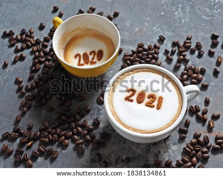 Goodbye 2020, Hello 2021 holidays food art theme coffee cups with number 2021 and 2020 on frothy surface flat lay on grey cement background with coffee beans. Holidays food art for Happy New Year. #1838134861