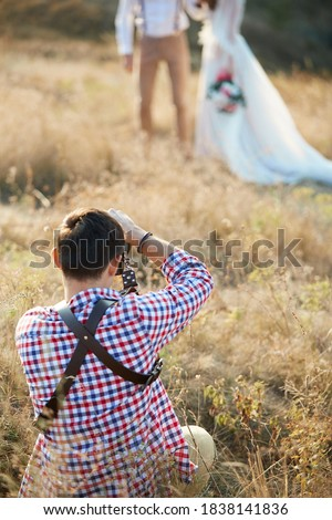 wedding professional photographer takes pictures of the bride and groom in nature on the sunset, man photographer in action