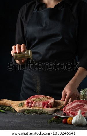 Professional chef in black uniform pours ground pepper on raw steak on wooden chopped board on dark blue background. Backstage of preparing grilled pork or beef. Dish from recipe book.