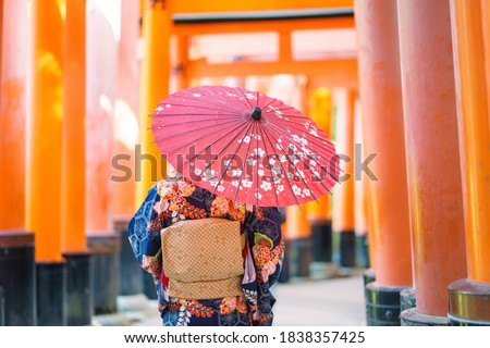 """Geishas girl wearing Japanese kimono among red wooden Tori Gate at Fushimi Inari Shrine in Kyoto, Kimono is a Japanese traditional garment. The word """"kimono"""", which actually means a """"thing to wear"""" Royalty-Free Stock Photo #1838357425"""