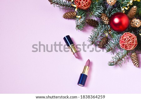 Cosmetic beauty product for holiday makeup for Christmas. Pink lipsticks in the form of a gift with xmas decor on a pink background. Winter sales of cosmetics. Copy space, flat lay.