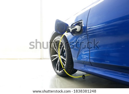 Selective focus of The power supply plug that is connected to the electric vehicle or EV car while charging the battery with bright light on car as background.  Royalty-Free Stock Photo #1838381248