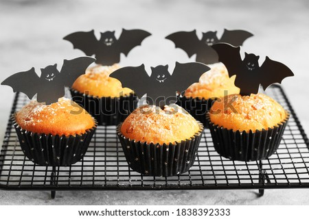 Halloween pumpkin muffins in black capsules decorated with cardboard bats. Festive Halloween cupcakes. Close-up view of delicious spooky halloween muffins on the grey background. Halloween recipes #1838392333