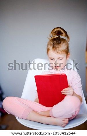Distance learning online education, young caucasian schoolgirl with tablet laptop doing school homework, child watching cartoons in a digital tablet at home