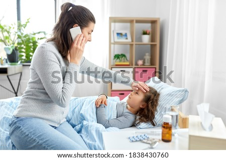family, health and people concept - ill daughter and mother with smartphone calling doctor at home