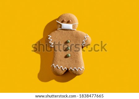Pandemic Christmas. Celebration restriction. Coronavirus winter holidays protective measures. New normal. Brown gingerbread man in medical face mask alone isolated on orange copy space background. Royalty-Free Stock Photo #1838477665