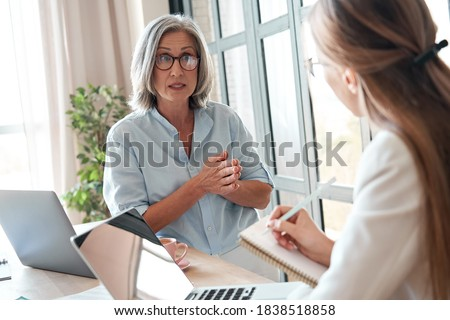 Mature old female mentor or manager training young intern explaining sharing professional skills in office. Middle aged senior business woman teacher speaking to student teaching trainee at meeting. Royalty-Free Stock Photo #1838518858