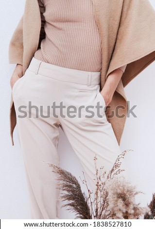 Stylish Pants and sweater. Details of everyday look. Model wearing casual beige outfit. Trendy minimalistic style. Beige aesthetics. Fashion look book. Warm Fall Winter seasons Royalty-Free Stock Photo #1838527810
