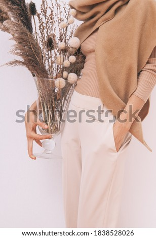Stylish Lady in beige outfit with flowers decor.  Details of everyday look. Trendy minimalistic style. Beige aesthetics. Fashion look book. Warm Fall Winter seasons concept Royalty-Free Stock Photo #1838528026