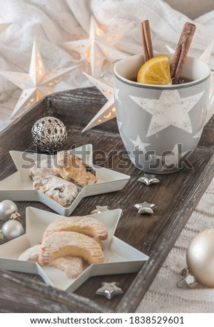 Cup of tea or punch and Christmas pastries on a wooden tray on a white blanket, decorated with christmas ball, little stars and star fairy lights. Vertical stock photo. #1838529601