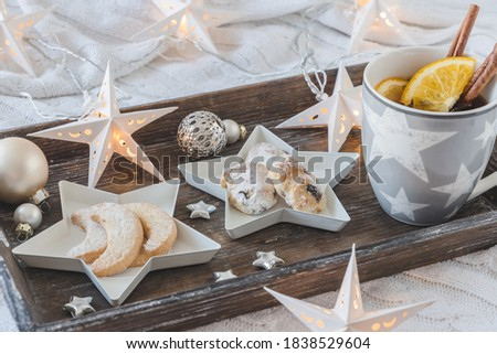 Cup of tea or punch and Christmas pastries on a wooden tray on a white blanket, decorated with christmas ball, little stars and star fairy lights #1838529604