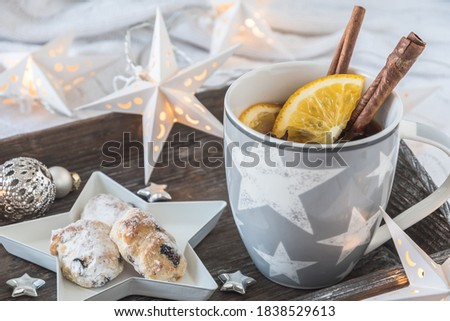 Cup of tea or punch and mini stollenon a wooden tray on a white blanket, decorated with christmas ball, little stars and star fairy lights #1838529613