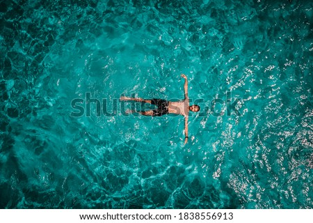 Drone areal view of young male in swimming pool floating Royalty-Free Stock Photo #1838556913