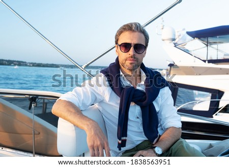 Handsome good looking mature man on the yacht. Portrait of successful man on sailing boat at sunset. Royalty-Free Stock Photo #1838563951