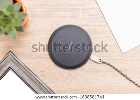 """Modern wireless charger for devices, phones and electronics. Smart phone charger on a table, with inscription """"Wireless charger"""" on the top. Royalty-Free Stock Photo #1838581741"""