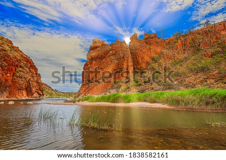 Outback landscape with red rocks and Finke river passage at Glen Helen gorge in the West Macdonnell Ranges of the Northern Territory in Australia with sun rays opening through rocky peaks Royalty-Free Stock Photo #1838582161
