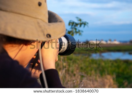 photographer taking pictures of wildlife with a telephoto lens