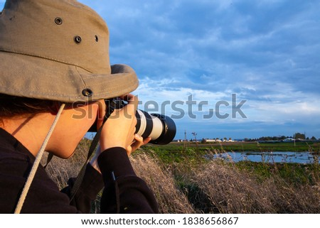 photographer taking pictures of wildlife with a lens