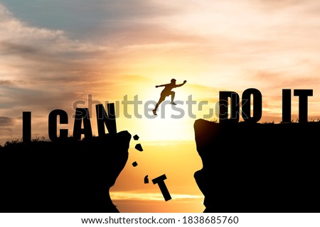Silhouette man jumping over cliffs for I can do it , good mindset by never give up concept. Royalty-Free Stock Photo #1838685760