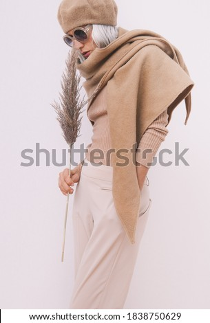 Stylish Details of everyday look. Model wearing casual beige outfit. Beret, scarf and fashion sunglasses. Trendy minimalistic style. Royalty-Free Stock Photo #1838750629