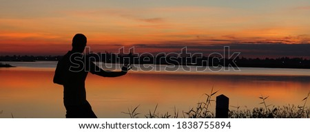 A man who dances in kung fu by the river at sunset. Using a silhouette technique. Royalty-Free Stock Photo #1838755894